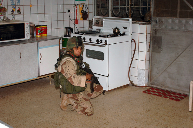 Soldiers from the 4th Iraqi Army Brigade and Delta , 1ST Battalion, 87th Infantry conduct a joint patrol in Ameriyah, Iraq on April 27, 2006. The purpose of the patrol was to search for illegal weapons and to give local people a feeling of security.  An Iraqi soldier provides security as fellow soldiers search the inner and outter parts of a home.(U.S. Army photo by STAFF SGT. Kevin L. Moses Sr.) (Released)