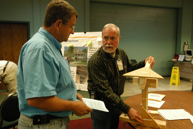 [Hurricane Katrina] Gautier, Miss., April 27, 2006 - At the FEMA ESF-14 Long Term Community Recovery Meeting, FEMA Mitigation Specialist Jerry Powers (right) and Jackson County contractor Charles Givens discuss methods of strengthening buildings against disaster damage.  George Armstrong/FEMA