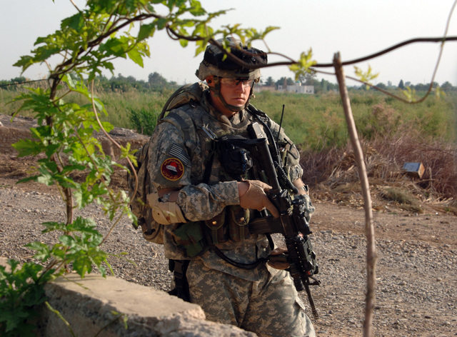 STAFF SGT. Michael Deason from B Battery 3-320th Field Artillery Regiment, 101st Airborne Division guards outside a house's fence during Operation Savage Strike in the western desert of Tikrit on April 30, 2006. Operation Savage Strike was a search for possible weapons caches conducted by Soldiers from 3-320th Field Artillery Regiment, 101st Airborne Division and 4th Iraqi Army Division. (U.S. Army photo by SPC. Teddy Wade) (Released)