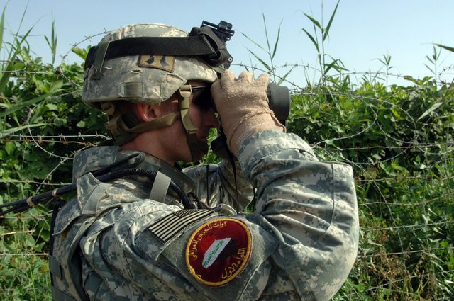 U.S. Army CPT. John Montgomery, commander of B Battery 3-320th Field Artillery Regiment, 101st Airborne Division observes a field through the binoculars during Operation Savage Strike in the western desert of Tikrit on April 30, 2006.   Operation Savage Strike was a search for possible weapons caches conducted by Soldiers from 3-320th Field Artillery Regiment, 101st Airborne Division and 4th Iraqi Army Division.(U.S. Army photo by SPC. Teddy Wade) (Released)