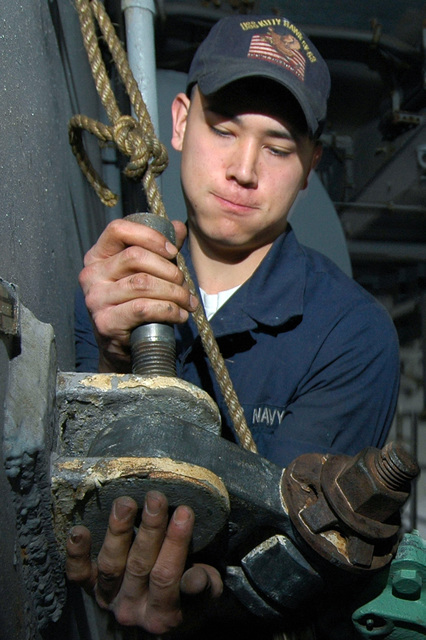 Onboard the USN Navy (USN) Aircraft Carrier, USS KITTY HAWK (CV 63), SEAMAN (SN) Gavin Takata inserts a bolt into a DD rig block. The DD rig is a system of pulleys used to help guide fuel hoses from refueling ships during Replenishment At Sea (RAS). The KITTY HAWK is currently in port at Yokosuka, Japan