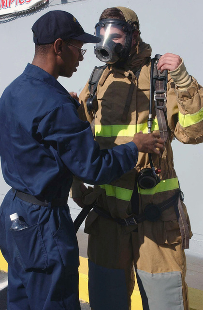 US Navy (USN) Damage Controlman Third Class (DC3) Jason Parrott (left) assists his teammate USN Hull Maintenance Technician Fireman (HTFN) Jeff Dahl, with his fire fighting gear including the Self Contained Breathing Apparatus, during the Dress Out Drill held aboard the USN Ticonderoga Class: Guided Missile Cruiser (Aegis) USS SAN JACINTO (CG 56), during the Damage Control Competition sponsored by the Resolve Marine Group during Fleet Week USA in Port Everglades, Florida (FL)