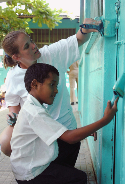 US Navy (USN) Electronic Warfare Officer (EWO), ENSIGN (ENS) Michelle Mazer, assigned to Oliver Hazard Perry Class Frigate USS UNDERWOOD (FFG 36) and a Honduran boy work together to paint a door to a small schoolhouse during a community relations project in Puerto Castilla. The UNDERWOOD is part of the George Washington Carrier Strike Group (CSG) participation in Partnership of the Americas 2006, a maritime training and readiness deployment of the US Naval Forces with Caribbean and Latin American countries in support of the US Southern Command (SOUTHCOM) objectives for enhanced maritime security