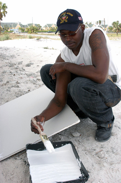 US Navy (USN) SEAMAN (SN) Charlie Little, assigned aboard the USN Arleigh Burke Class (Flight II): Guided Missile Destroyer (Aegis), USS OSCAR AUSTIN (DDG 79), paints the outer walls of a new home for a Habitat for Humanity project in Pompano, Florida (FL). Little is one of nearly 3,000 sailors are participating in this year's South Florida Fleet Week USA. As part of the Navy's commitment to the community, Navy volunteers will carry out community service projects such as home building, visiting local schools, and patients at local hospitals