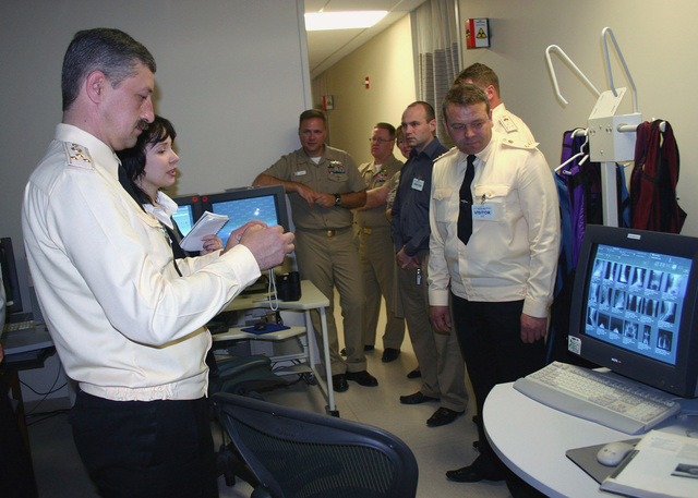 While on a tour of US Naval Hospital - Naples, Ukrainian medical officers look at digital X-rays in the radiology Department. The Ukrainian delegation spent three days in the area to share Human Immunodeficiency Virus (HIV) awareness, prevention and treatment information with their American counterparts