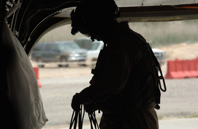 U.S. Army STAFF SGT. Robert Irvina, Bravo Company, 6th Battalion, 101st Command Aviation Brigade, 101st Airborne Division (Air Assault), prepares for a flight on a CH-47 Chinook helicopter at Forward Operating Base Remagen, Tikrit, Salah ad Din Province, Iraq, on May 7, 2006, in support of Operation Iraqi Freedom.  (U.S. Army photo by SPEC. Teddy Wade) (Released)