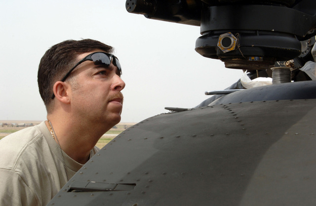 U.S. Army STAFF SGT. Robert Urvina, Bravo Company, 6th Battalion, 101st Command Aviation Brigade, 101st Airborne Division (Air Assault), performs a pre-flight inspection on the front engine of a CH-47 Chinook Helicopter at Forward Operating Base Remagen, Tikrit, Salah ad Din Province, Iraq, on May 7, 2006, in support of Operation Iraqi Freedom.  (U.S. Army photo by SPEC. Teddy Wade) (Released)