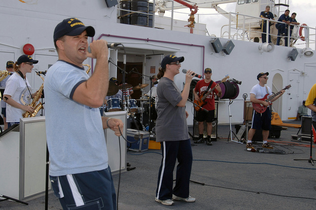 US Navy (USN) Musician Second Class (MU2) Brandon Barbee (foreground), assigned to the USN Show Band from Norfolk, Virginia (VA), performs for Sailors on the flight decks of the USN Military Sealift Command (MSC), Hospital Ship, USNS MERCY (T-AH 19). The USNS MERCY is currently underway in the Pacific Ocean, conducting a scheduled five-month deployment to deliver aid and humanitarian assistance to the Pacific Islands, and Southeast Asia