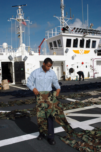 Onboard the flight deck of the US Navy (USN) Military Sealift Command (MSC), Hospital Ship, USNS MERCY (T-AH 19), USN Hospitalman (HM) Gerry Newsome prepares uniforms to be sprayed with Permethrin. Permethrin is effective against multiple species of crawling and flying insects, including mosquitoes, ticks, fleas, bedbugs, chiggers and flies. The USNS MERCY is currently underway in the Pacific Ocean, conducting a scheduled five-month deployment to deliver aid and humanitarian assistance to the Pacific Islands, and Southeast Asia.2006) Hospitalman Gerry Newsome of San DiegoCalif.prepares uniforms to be sprayedwith Permethrin on the flight deck aboard the Military Sealift Command (MSC)...