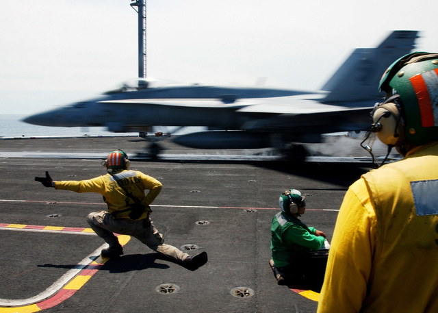 "A US Navy (USN) (yellow shirt) Catapult Safety Officer, signals as a USN F/A-18C Hornet aircraft assigned to the ""Gladiators"" of Fighter Attack Squadron 106 (VFA-106) launches off the flight deck of the USN Nimitz Class Aircraft Carrier, USS THEODORE ROOSEVELT (CVN 71). The ROOSEVELT is currently underway in the Atlantic Ocean maintaining qualifications as part of the Navy's Fleet Response Plan"