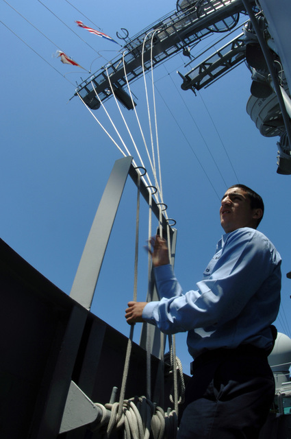 On board the US Navy (USN) Nimitz Class Aircraft Carrier USS THEODORE ROOSEVELT (CVN-71), USN Quartermaster SEAMAN (QMSN) Felix Delao helps raise a signal pennant on the signal bridge. The ROOSEVELT is currently underway in the Atlantic Ocean maintaining qualifications as part of the Navy's Fleet Response Plan
