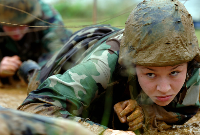 "A female US Naval Academy Midshipmen crawls the mud as she participates in ""Sea Trials"" at Hospital Point at the US Naval Academy in Annapolis, Maryland (MD). Modeled after the US Marine Corps' ""Crucible"" and Navy's ""Battle Stations"" programs, Sea Trials is a capstone event for the freshmen midshipmen and also a leadership challenge for the Upperclassmen"