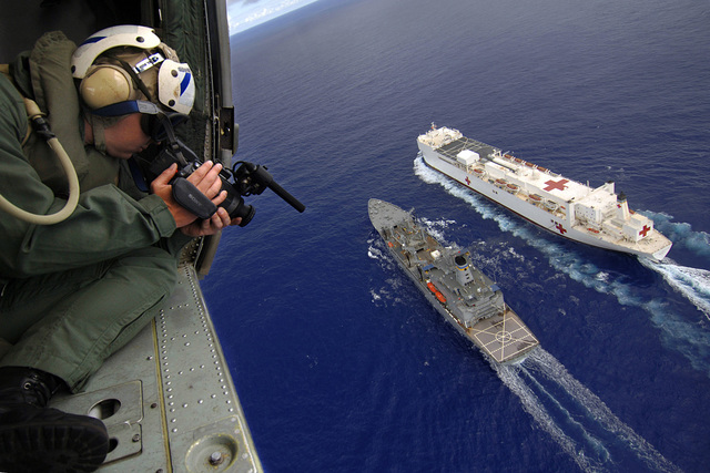 US Navy (USN) Photographer's Mate Second Class (PH2) Gregory E. Badger, uses a digital video recorder to document activities from his aerial platform, of Replenishment At Sea (RAS) operations being conducted between the US Navy (USN) Military Sealift Command (MSC), Henry J. Kaiser Class: Oiler, USNS PECOS (T-AO197) and the USN MSC Hospital Ship, USNS MERCY (T-AH 19), while the ships are underway in the Pacific Ocean, during a scheduled five-month deployment to deliver aid and humanitarian assistance to the Pacific Islands and Southeast Asia.2006) Photographer's Mate 2nd Class Gregory E. Badger videotapes an underway-replenishment operation between the Military Sealift Command(MSC)...