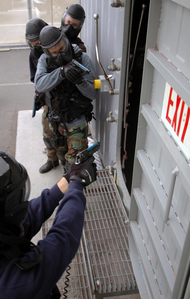 US Navy (USN) Sailors assigned aboard the USN Arleigh Burke Class (Flight I): Guided Missile Destroyer (Aegis), USS MILIUS (DDG 69), armed with M9 9mm training weapons equipped to fire simunition rounds, and wearing paintball protective face masks, prepare to advance through a watertight door during training at the Center for Security Forces at Naval Station (NS) San Diego, California (CA)