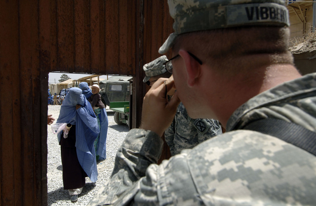 SPC. Robert Vibbert (left) from the 14th Combat Support Hospital, Task Force Med Falcon, takes a photo of a local Afghan women coming in to the Humanitarian Civic Aid point during a Medical Civic Assistance Program (MEDCAP) at the Egyptian Hospital. (U.S. Army photo by SPC. Leslie Angulo) (Released)
