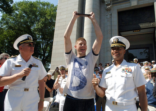 US Navy (USN) Vice Admiral (VADM) Rodney P. Rempt (left), Superintendent of the US Naval Academy, and USN Captain (CAPT) Bruce Grooms (right), Commandant Captain, congratulate Midshipman 4th Class Brian Richards at the conclusion of the 99th annual Herndon Climb, at the Naval Academy in Annapolis, Maryland (MD). Midshipmen work together to climb to the top of the 21-foot gray obelisk, (which is covered in more than 200 pounds of lard) and retrieve a white plebe dixie-cup hat. According to legend, the plebe who replaces the white hat with a midshipman's cover will become the first member of the class to become an admiral. Richards reached the top in 1:14:15