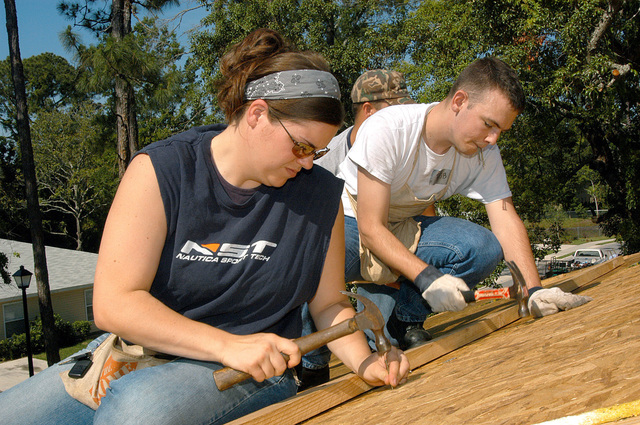 US Navy (USN) Gunners Mate Second Class (GU2) Amy Hamilton (foreground), and USN Intelligence SPECIALIST Third Class (IS3) Robert Steele, both assigned to the USN Nimitz Class Aircraft Carrier USS JOHN F. KENNEDY (CV 67), nails down plywood atop a roof during a community relations project for the local Habitat for Humanity chapter in Atlantic Beach, Florida (FL)