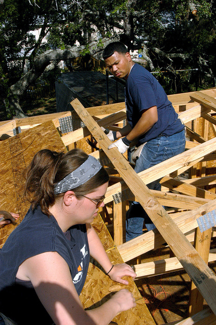 US Navy (USN) GUNNER's Mate Second Class (GU2) Amy Hamilton (foreground), assigned to the USN Nimitz Class Aircraft Carrier USS JOHN F. KENNEDY (CV 67), nails down plywood atop a roof during a community relations project for the local Habitat for Humanity chapter in Atlantic Beach, Florida (FL)