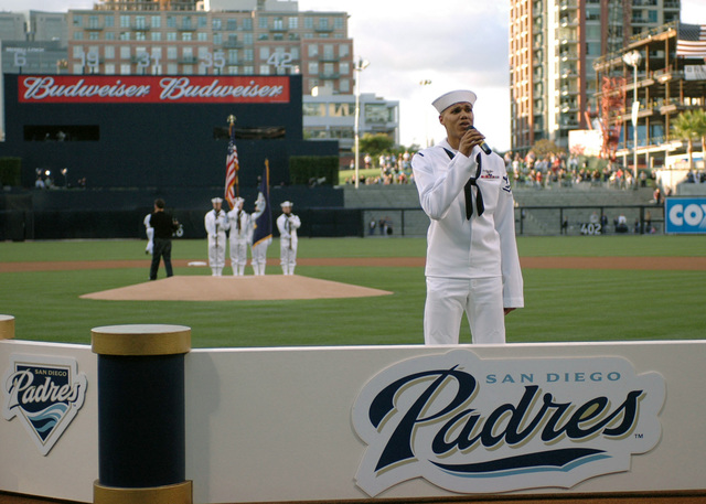 US Navy (USN) Air Traffic Controller Third Class (AC3) John Phillips (center) sings the national anthem while a USN Honor Guard holds the American Flag in the background prior to a Major League Baseball (MLB) game between the San Diego Padres and Atlanta Braves at PETCO Park, San Diego, California (CA). The San Diego Padres honored USN Sailors from the US Navy (USN) Aircraft Carrier Nimitz (CVN 68) in recognition of Armed Forces Appreciation Day