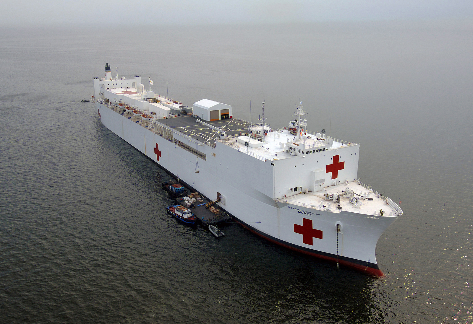 An aerial quarter starboard bow view of the US Navy (USN) Military Sealift Command (MSC), Hospital Ship, USNS MERCY (T-AH 19), resting at anchor in the Philippine Sea off of the coast of the Philippine capitol of Manila. The USNS MERCY is on a scheduled five-month deployment to deliver aid and humanitarian assistance to the Pacific Islands, and Southeast Asia
