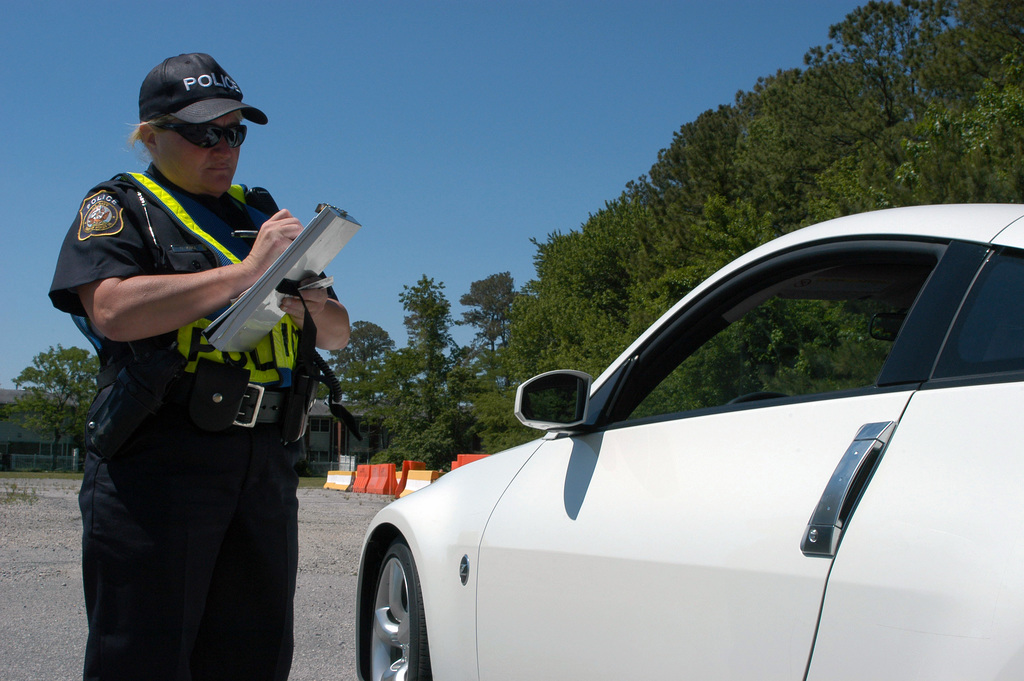 """Corporal (CPL) Gale Knight, a police officer with the Naval Amphibious Base Little Creek (NABLC) Police Department, writes a ticket to a driver for not wearing a seat belt during the base-wide""""Click It or Ticket Campaign"""". The campaign is a nationwide effort to enforce seat belt laws and ensure drivers are implementing safety on the road"""
