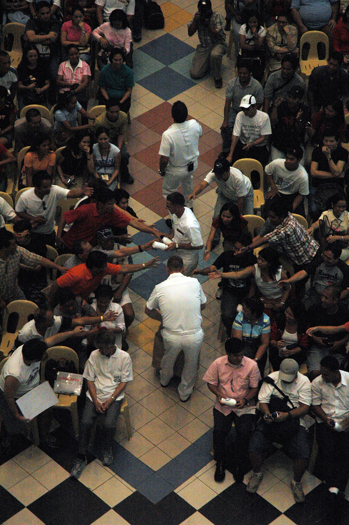 US Navy (USN) Sailors from the USN Atlantic Fleet Show Band, stationed aboard the USN Military Sealift Command (MSC), Hospital Ship, USNS MERCY (T-AH 19), distribute water bottles to the audience during an open concert at the Robinson Place Mall in Manila, Philippines.  The USNS MERCY is on a five-month humanitarian assistance deployment to South Asia, Southeast Asia and the Pacific Islands