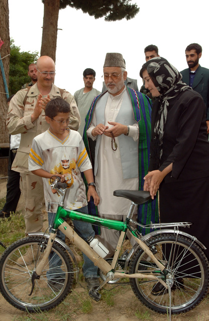 Afghan Parwan Province Governor, Jabar Taqwa, LTC Donald Koehler, Bagram, Provincial Reconstruction Team Commander, with Minister of Education, Samia Aziz-Satat hand out a bicycle to a local Afghan boy during the Norman High School grand opening in Charikar.  A number of students from 7th grade are awarded bicycles for outstanding academic achievements. (U.S. Army photo by SPC. Michael Zuk) (Released)