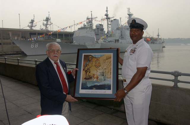 Mr. James Luzzi, Executive Director of the Anzio Memorial Ceremony and US Navy (USN) Command MASTER CHIEF (CMDCM) William Seegars pose for a photograph while holding a picture of the USS ANZIO World War Two (WWII) Memorial in New York City for Fleet Week New York 2006. The Anzio Memorial Monument ceremony honors those who fought at the Battle of Anzio during World War Two (WW II) for which the current US Navy (USN) Ticonderoga Class: Guided Missile Cruiser, USS ANZIO (CG 68), visible in the background, is named after. Fleet week activities include dozens of military demonstrations and displays throughout the week, as well as public visitation to many of the participating ships