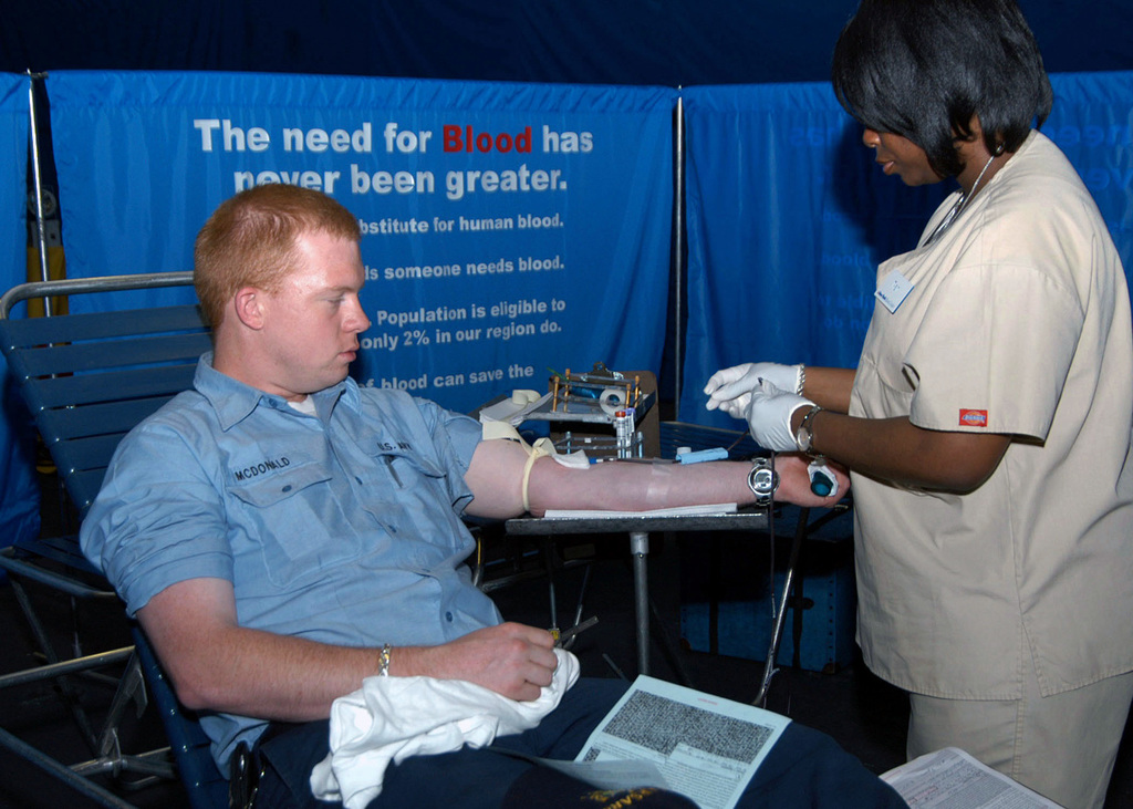 Nitisha Moore, a New York City Blood Center Worker, draws blood from US Navy (USN) Electrician's Mate Third Class (EM3) Jason McDonald during a blood drive conducted in the hangar bay aboard the USN Wasp Class: Amphibious Assault Ship, USS KEARSARGE (LHD 3). The blood drive is one of several community relation projects, in which the KEARSARGE and its crew are participating in during Fleet Week New York 2006. Fleet week activities include dozens of military demonstrations and displays throughout the week, as well as public visitation to many of the participating ships