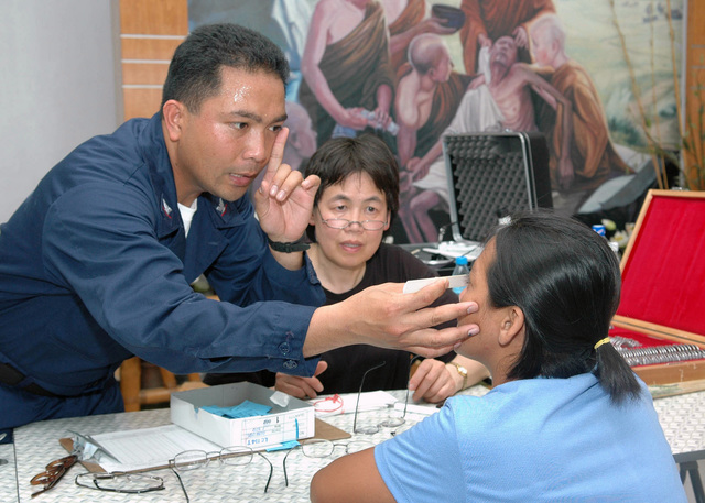 US Navy (USN) PETTY Officer Third Class (PO3) Misac Lopez (background left), and US Air Force (USAF) Lieutenant Colonel (LTC) Doris Wong perform an eye exam on a local patient at the Zamboanga Medical Center. Both LTC Wong and PO3 Lopez are attached to the US Navy (USN) Military Sealift Command (MSC), Hospital Ship, USNS MERCY (T-AH 19), and are helping to examine more than 250 patients and distributed some 200-pairs of glasses to the local residents of the Republic of Philippine City of Zamboanga. The USNS MERCY is on a scheduled five-month deployment to deliver aid and humanitarian assistance to the Pacific Islands, and Southeast Asia