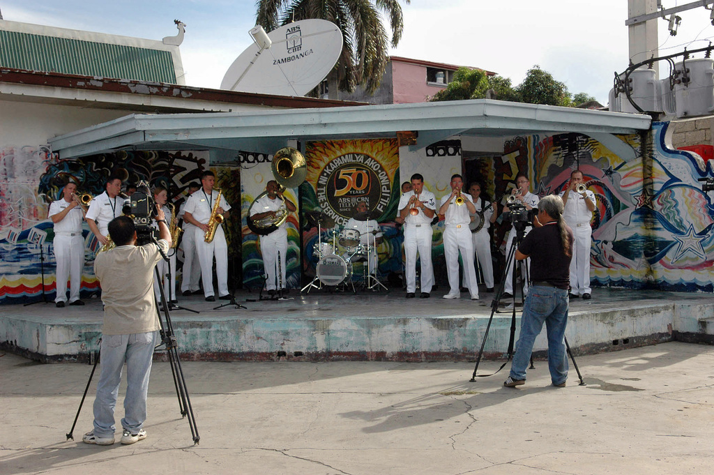 Members of the local city news channel document US Navy (USN) Musicians from the USN Show Band during a scheduled humanitarian visit by the USN Military Sealift Command (MSC), Hospital Ship, USNS MERCY (T-AH 19), in the Republic of Philippines City of Zamboanga. The USNS MERCY is on a scheduled five-month deployment to deliver aid and humanitarian assistance to the Pacific Islands, and Southeast Asia