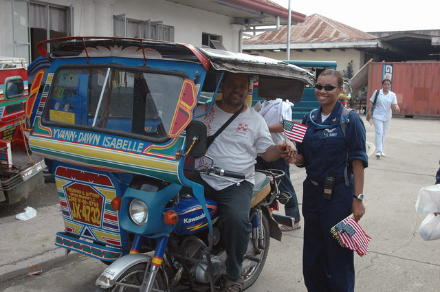 US Navy (USN) PETTY Officer Third Class (PO3) Adelaida Sojo (foreground right), from the USN Military Sealift Command (MSC), Hospital Ship, USNS MERCY (T-AH 19), hands out American Flags to local Filipino resident in front of the Zamboanga Medical Center in Zamboanga, Republic of the Philippines. The USNS MERCY is on a scheduled five-month deployment to deliver aid and humanitarian assistance to the Pacific Islands, and Southeast Asia