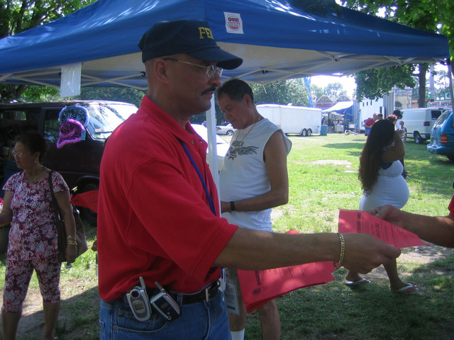 Lawrence, MA, June 18, 2006 -- Community Relations (CR) field officer Jorge Gonzales hands out fliers at the Semana Hispana Festival in Lawrence, Massachusetts.  FEMA/Hannah Vick