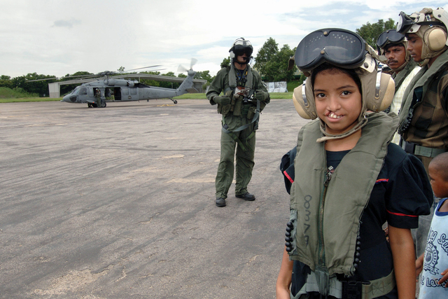 A young Bengali girl prepares to board a US Navy (USN) MH-60S Sea Hawk helicopter assigned to Sea Combat Squadron 25 (HSC-25), to be flown aboard the USN Military Sealift Command (MSC), Hospital Ship, USNS MERCY (T-AH 19), stationed off shore. The girl will undergo cleft lip surgery during the Ship's visit to provide humanitarian and civic assistance to the people of Bangladesh. The MERCY is on a scheduled five-month deployment to deliver aid and humanitarian assistance to South and Southeast Asia and the Pacific Islands