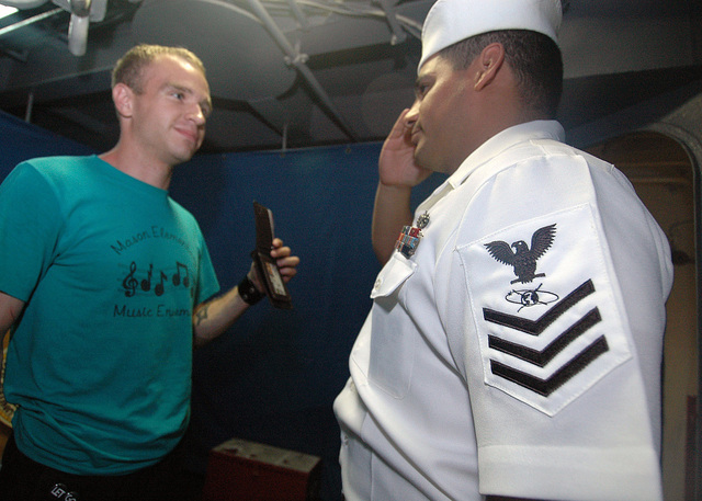 US Navy (USN) Mass Communication SPECIALIST First Class (MC1) Authur Delacruz (right), report for duty as the first PETTY Officer of the Watch under the new Mass Communication SPECIALIST rating aboard conventionally-powered aircraft carrier USS JOHN F. KENNEDY (CV 67). The new rating, which combined the former ratings of Photographer's Mate, Draftsman, Journalist and Lithographer, became effective July 1, 2006. The KENNEDY is currently in port at Naval Station Mayport, Florida (FL)