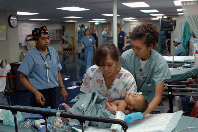 Onboard the US Navy (USN) Military Sealift Command (MSC), Hospital Ship, USNS MERCY (T-AH 19), USN Lieutenant Junior Grade (LTJG) Cathrine Soteras (right) helps Operation Smile Nurse, Jhen Valdez, with a small child in a recovery room after a cleft lip surgery performed by Operation Smile Doctors. The Ship is currently anchored approximately 15 nautical miles off the coast of Chittagong, Bangladesh. The MERCY is on a scheduled five-month deployment to deliver aid and humanitarian assistance to South and Southeast Asia and the Pacific Islands