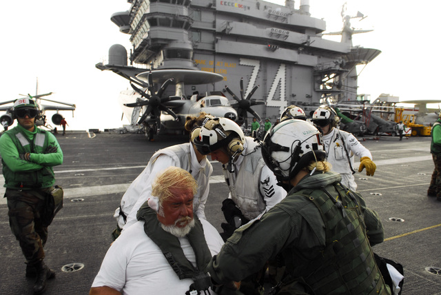 Onboard the flight deck of the US Navy (USN) Nimitz Class Aircraft Carrier USS JOHN C. STENNIS (CVN 74), an unidentified civilian sports fisherman is fitted with safety gear, in preparation for a transport flight to Naval Station (NS) North Island, California (CA). The fisherman was rescued from his stranded fishing boat in the Pacific Ocean, by USS STENNIS crew members, and is being airlifted after being treated for head injuries by the ship's medical staff. The STENNIS and its embarked Carrier Air Wing 9 (CVW-9) are currently underway in the Pacific Ocean conducting a Tailored Ship's Training Availability (TSTA)