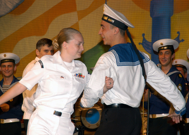 US Navy (USN) Operations SPECIALIST Second Class (OS2) Elizabeth Sessions from the USN Amphibious Command Ship (LCC) Blue Ridge (LCC 19) dances with a Russian Federated Navy (RFN) Sailor during a traditional folk music performance by the Russian Pacific Fleet (RPF) Song and Dance Ensemble at Vladivostok, Russia (RUS). The two-hour performance told proud stories about the Russian Federated Navy (RFN) history. The American Sailors are in Vladivostok to foster camaraderie between the USN and RFN during their four-day visit