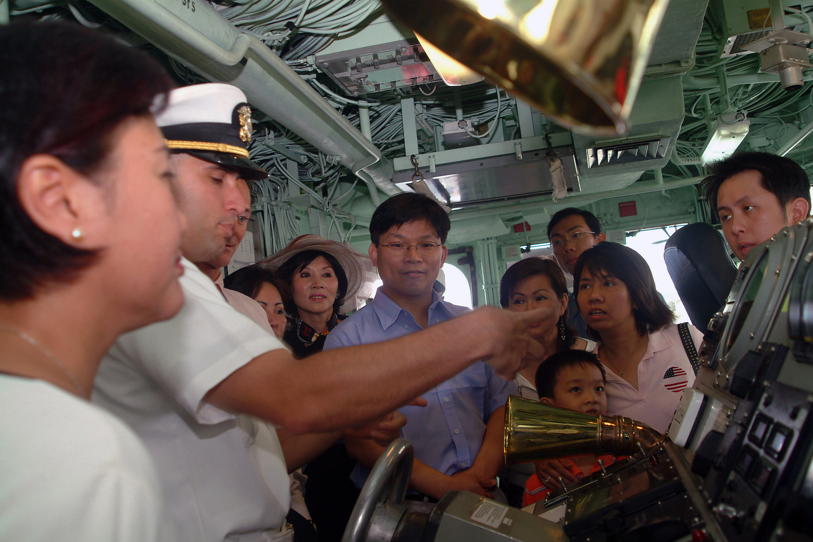 A US Navy (USN) Sailor (left) gives members of the People's Army of Vietnam (PAVN) and their family a tour aboard the USN Avenger Class Mine Countermeasures Vessels USS PATRIOT (MCM 7) during their visit in Ho Chi Minh City, Vietnam (VNM). During their stay, the USN Sailors will interact with the Vietnamese people through a variety of events, including a community service project at a local orphanage. Visits to Vietnam by USN ships symbolize the continuation of relations between the two nations