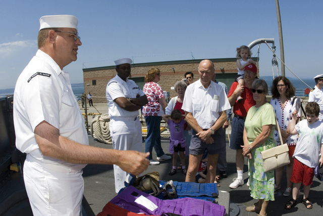 Onboard the US Navy (USN) Oliver Hazard Perry Class Guided Missile Frigate USS RODNEY M. DAVIS (FFG 60), USN Boatswain's Mate First Class (BM1) William Irons (foreground left) shows civilian guests how floatation jackets are used during the 4th of July Family Freedom Fest 2006 Celebration, held at Naval Air Station (NAS), Everett, Washington (WA)