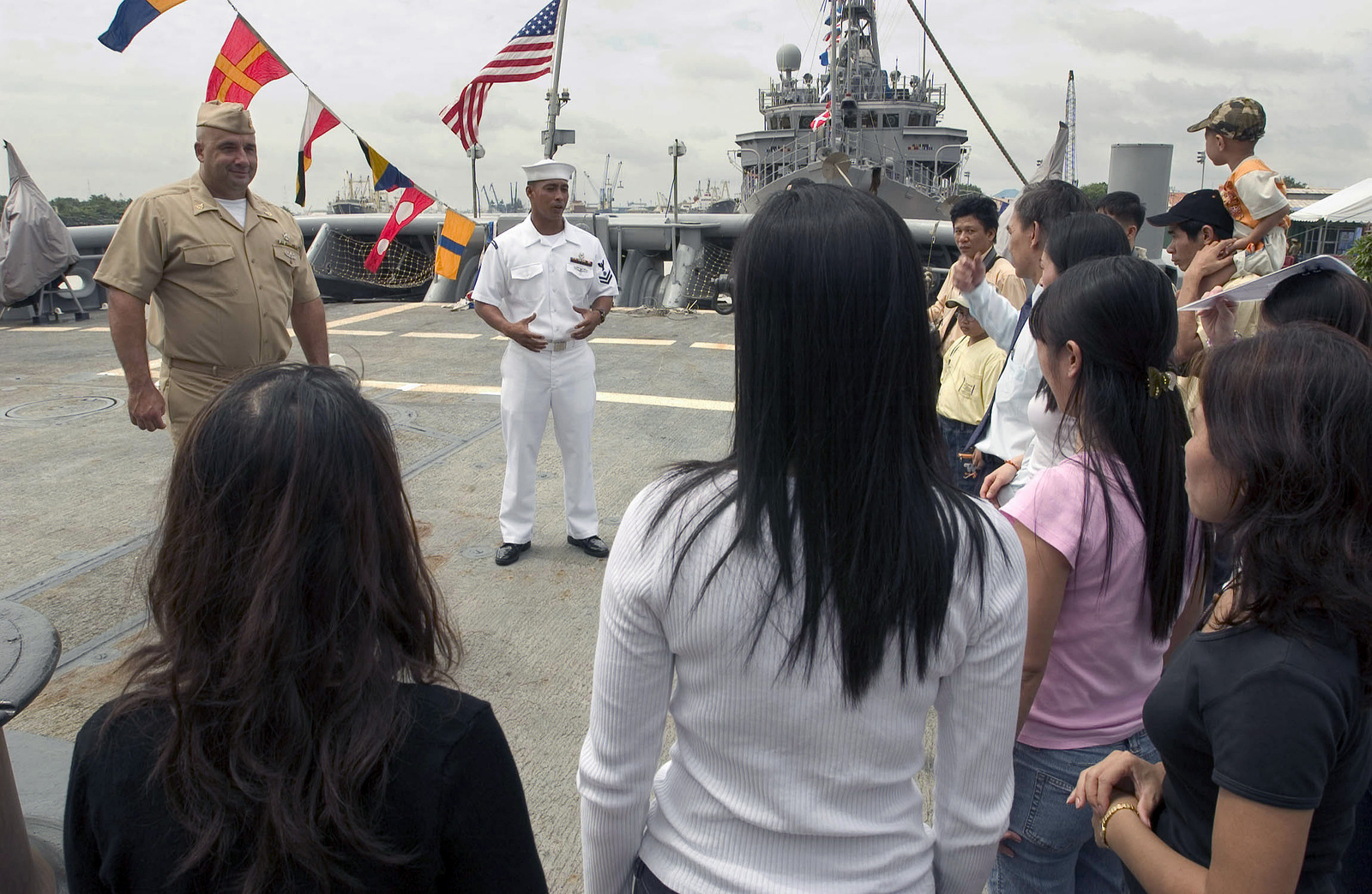US Navy (USN) SENIOR CHIEF Navy Diver (NDCS) Michael Moser (left) and Quartermaster Second Class (QM2) Jason Tangalin (center) shows local visitors how diving operations are conducted from the fantail of the USN Safeguard Class Salvage Ship USS SALVOR (ARS 52) during their visit in Ho Chi Minh City, Vietnam (VNM). During their stay, the USN Sailors will interact with the Vietnamese people through a variety of events, including a community service project at a local orphanage. Visits to Vietnam by USN ships symbolize the continuation of relations between the two nations