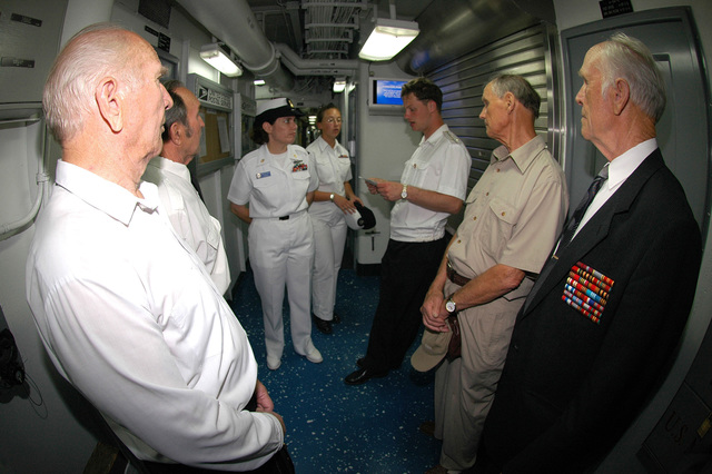 US Navy (USN) CHIEF MASTER-At-Arms (MAC) Mary McQuain explains the ship's post office operations to a group of Russian World War II (WWII) military veterans as they tour the USN Amphibious Command Ship USS BLUE RIDGE  (LCC 19) during the ship's visit at Vladivostok, Russia (RUS). The BLUE RIDGE and the embarked staff of the USN 7th Fleet are currently in Vladivostok to foster camaraderie between the USN and Russian Federated Navy (RFN)