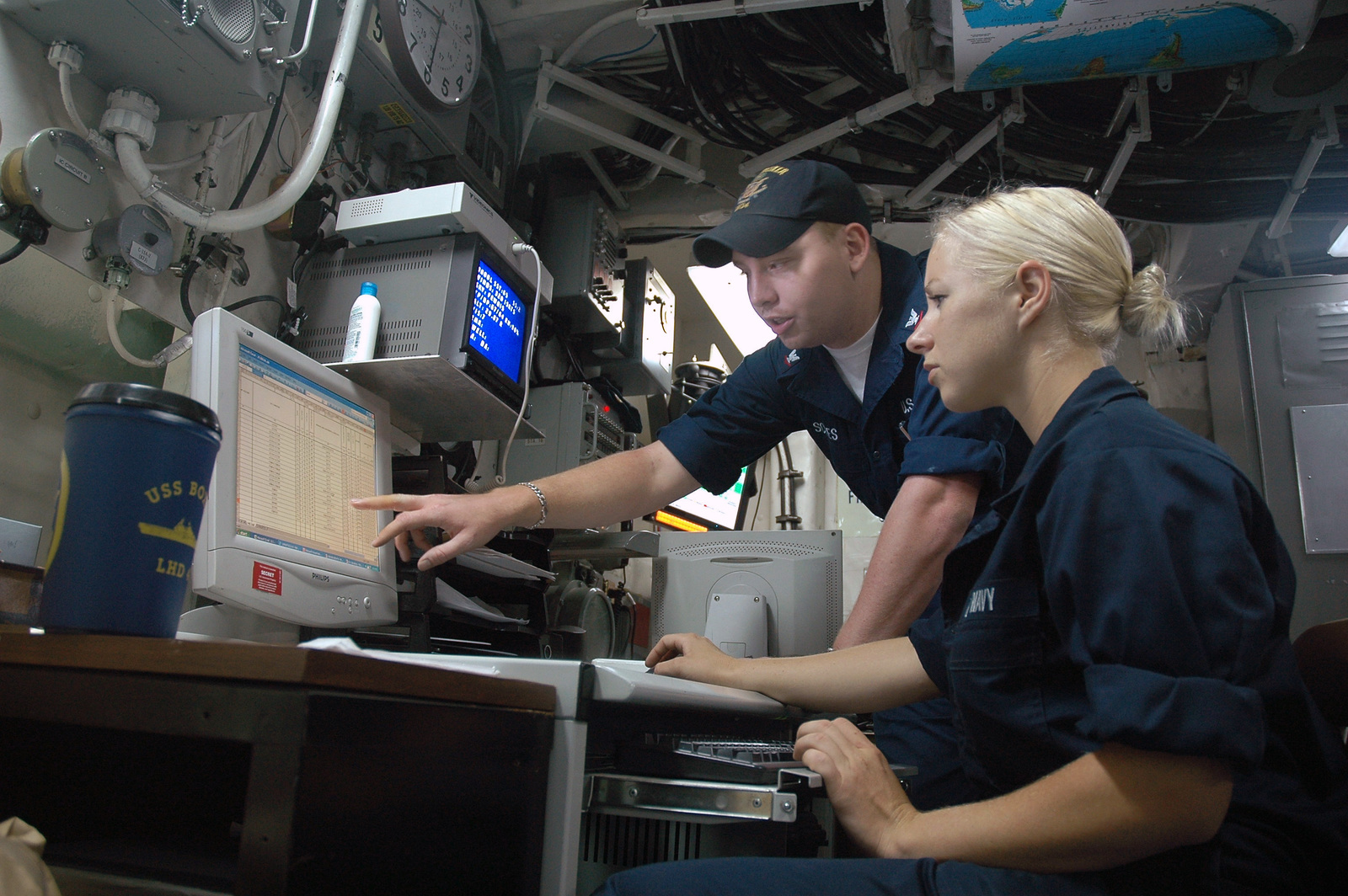 060721-N-5914D-001 (Jul. 21, 2006)US Navy (USN) Aerographer's Mate Third Class Daniel Scites (rear) shows USN SEAMAN Olivia Mailander how to read weather charts aboard the USN Wasp Class Amphibious Assault Ship USS BOXER (LHD 4).  The BOXER is part of Expeditionary Strike Group (ESG) 5 which is currently participating in the Composite Training Unit Exercise (COMPTUEX) off the coast of Southern California.U.S. Navy photo by Mass Communication SPECIALIST Third Class Noel Danseco (RELEASED)