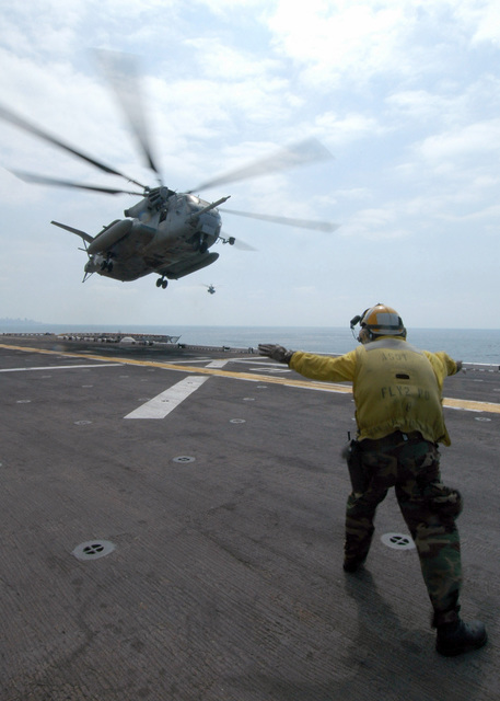 US Navy (USN) Aviation Boatswains Mate Handler Third Class (ABH3) Gavin J. Anderson helps to recover a US Marine Corps (USMC) Sikorsky CH-53E Sea Stallion cargo helicopter, Marine Medium Helicopter Squadron 365 (HMM-365), as it lands on the flight deck of the US Navy (USN) Wasp Class Amphibious Assault Ship USS IWO JIMA (LHD 7) while assisting American citizens as they arrive onboard after being evacuated from Lebanon
