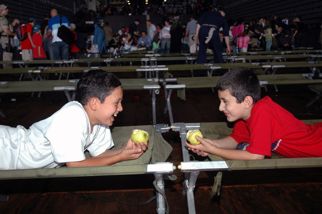 Two young boys enjoy an apple aboard the USN Austin Class Amphibious Transport Dock Ship USS TRENTON (LPD 14). The TRENTON is on a regularly scheduled deployment, and is assisting the US Central Command (US CENTCOM) and 24th Marine Expeditionary Unit (MEU) with the departure of US citizens from Lebanon, at the request of the US Ambassador to Lebanon and at the direction of the Secretary of Defense (SECDEF). Lebanon is under an Israeli attack in retaliation against Hezbollah guerillas, for a raid into northern Israel and the capture of two Israeli Soldiers