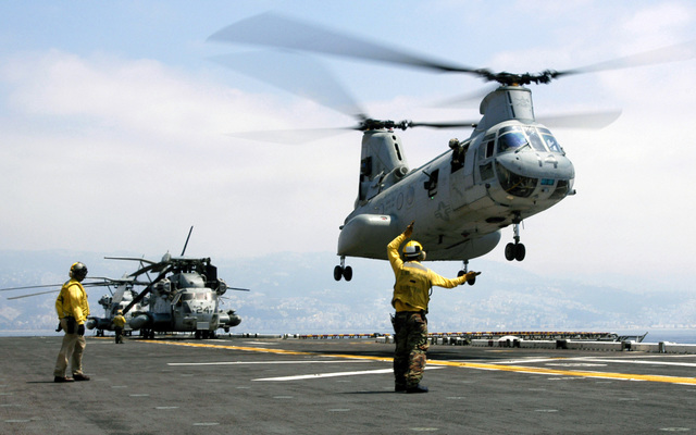 US Navy (USN) Aviation Boatswains Mate Handler Third Class (ABH3) Gavin J. Anderson signals to a US Marine Corps (USMC) Marine Medium Helicopter Squadron 365 (HMM-365) Boeing CH-46D Sea Knight cargo helicopter as it lifts away from the flight deck of the USN Wasp Class Amphibious Assault Ship USS IWO JIMA (LHD 7), while the USS IWO JIMA is off the coast of Beirut, Lebanon (LBN), assisting American citizens as they arrive onboard after being evacuated from Lebanon