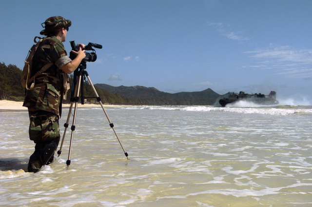 US Navy (USN) Mass Communication SPECIALIST Second Class (MC2) Summer Anderson, from Combat Camera Group Pacific, uses a video camera to document a USN Landing Craft Air-Cushion (LCAC) craft coming ashore a beach at Bellows Air Force Station (AFS), Hawaii (HI), during an amphibious assault training during Exercise Rim of the Pacific (RIMPAC) 2006. The exercise designed to increase the tactical proficiency of participating units in a wide array of combined sea operations. RIMPAC 2006 brings together military forces from Australia (AUS), Canada (CAN), Chile (CHL), Peru (PER), Japan (JPN), the Republic of Korea (KOR), United Kingdom (UK) and the United States (US)