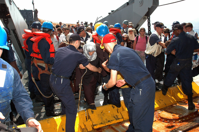 US Navy (USN) Sailors aboard the USN Austin Class Amphibious Transport Dock Ship USS TRENTON (LPD 14) assist US citizens evacuated from Beirut, Lebanon (LBN) as they arrive onboard Landing Craft Utility (LCU) 1643. The TRENTON is on a regularly scheduled deployment, and is assisting the US Central Command (US CENTCOM) and 24th Marine Expeditionary Unit (MEU) with the departure of US citizens from Lebanon, at the request of the US Ambassador to Lebanon and at the direction of the Secretary of Defense (SECDEF). Lebanon is under an Israeli attack in retaliation against Hezbollah guerillas, for a raid into northern Israel and the capture of two Israeli Soldiers