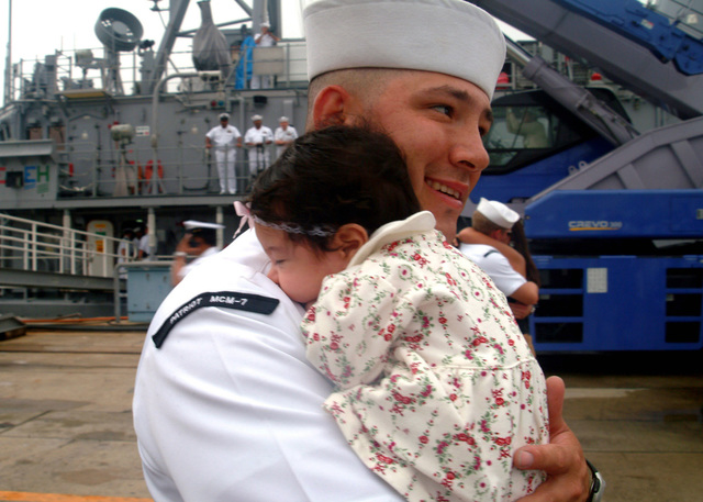 US Navy (USN) PETTY Officer 1ST Class Felipe Gallegos, Mineman 1ST Class holds his daughter after the arrival of the USN Avenger Class Mine Countermeasures Vessel USS PATRIOT (MCM 7) to its forward deployed homeport in Sasebo, Japan. The PATRIOT and embarked Explosive Ordnance Disposal Mobile Unit 5 (EODMU-5), Detachment 51 (Det-51) concluded a three-month deployment throughout Southeast Asia under Commander, Task Force 76 (CTF-76). (U.S. Navy photo by Mass Communication SPECIALIST 3rd Class Adam R. Cole) (Released)