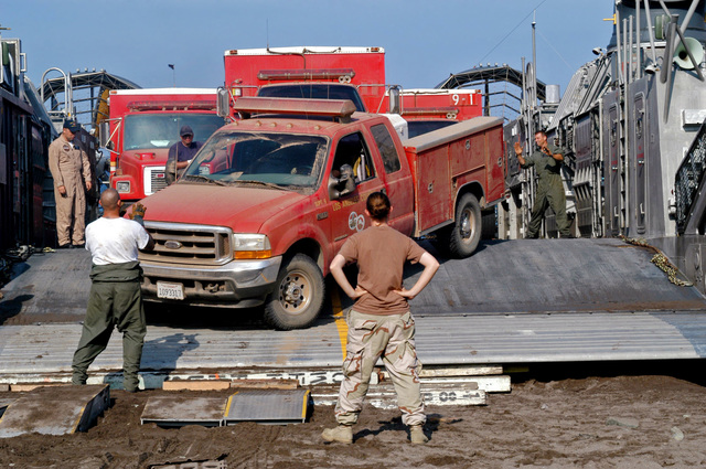 060725-N-6597H-102  (Jul. 25, 2006)US Navy (USN) Sailors, Assault Craft Unit 5 (ACU-5), assist with the loading of the Los Angeles Fire Department (LAFD) crew carrier vehicles, onto an amphibious Landing Craft Air Cushion (LCAC) at Catalina Island, California, (CA).U.S. Navy official photo by Mass Communication SPECIALIST SEAMAN (MCSN) Jonathan Husman (Released)